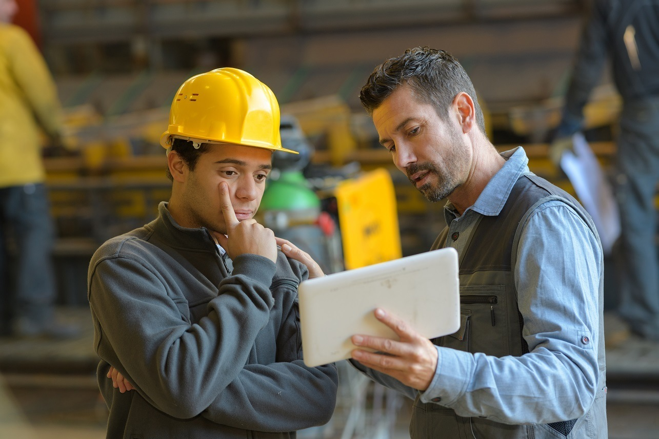foreman explaining to employee with tablet